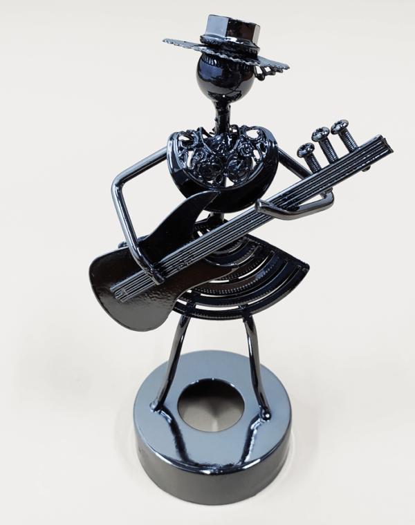 Figura decorativa metálica en forma de músico bajista